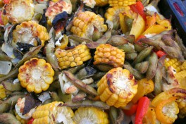 Charred corn on the cob, red peppers, cauliflower and edamame in a pan after roasting in the oven.