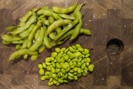 A pile of edamame in pods and a pile of already peeled kernels.