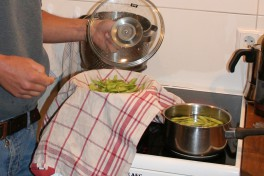 Edamame in a cooking pot on the stove. One person has poured a portion of edamame into a sieve covered with a kitchen cloth.